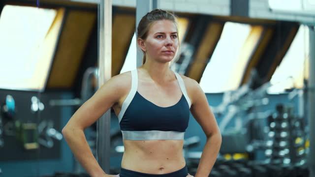 donna sportiva che si sposta sui piedi in una postura akimbo in palestra - mani sui fianchi video stock e b–roll