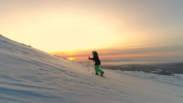 antenn: sportig kvinna snöskor mot den snötäckta bergstopp på golden sunrise - vintersport bildbanksvideor och videomaterial från bakom kulisserna