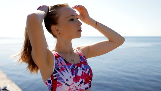 sporty woman ties hair before training at sea background - reggiseno sportivo video stock e b–roll