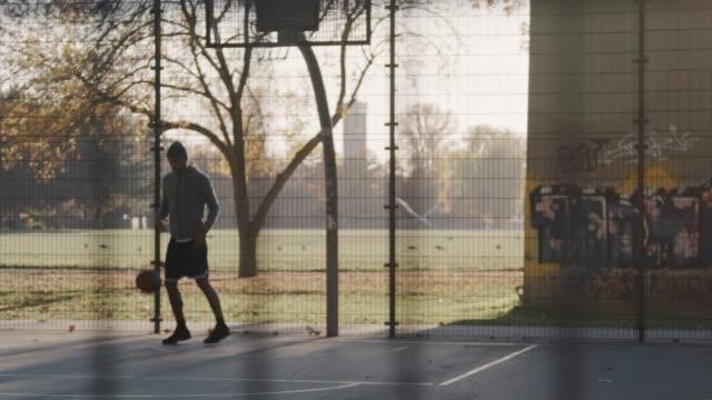 stockvideo's en b-roll-footage met sportieve jongeman gooien basketbal in de hoepel - fence