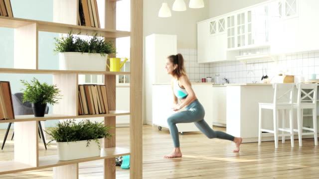 sportig ung kvinna gör utfall knäböj övning i vardagsrummet, sidovy - hemmaträning bildbanksvideor och videomaterial från bakom kulisserna
