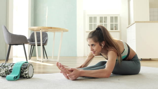vídeos de stock e filmes b-roll de sporty young woman making stretching exercise sitting at home leans to legs - treino em casa