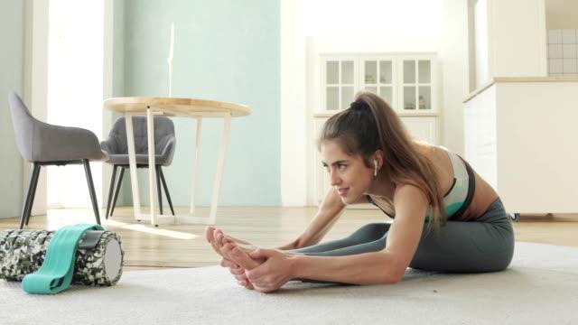 sportig ung kvinna gör stretching motion sitter hemma lutar sig mot benen - hemmaträning bildbanksvideor och videomaterial från bakom kulisserna