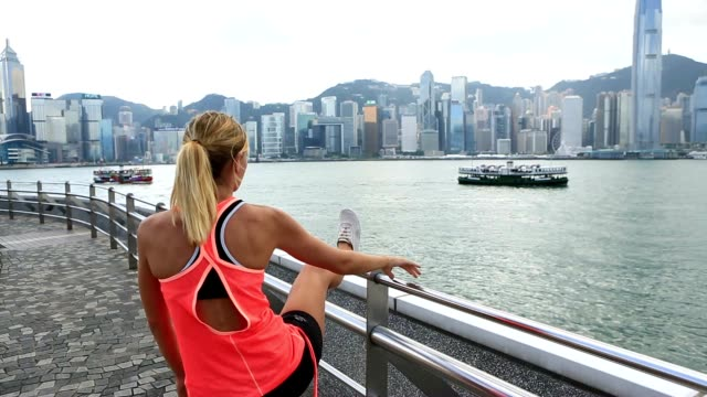 Sporty young woman stretching after jogging in Hon Kong video