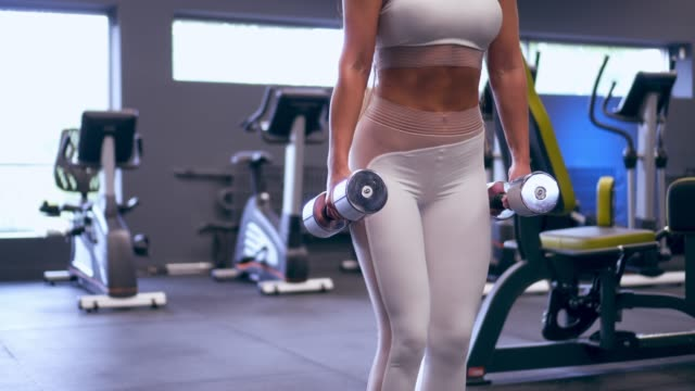 Sporty young woman working out with dumbbells video