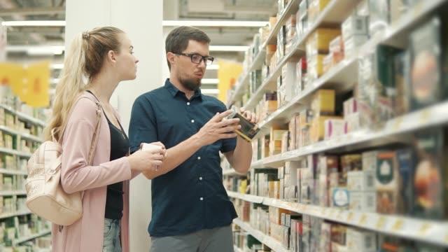 Conjoints font des emplettes dans une épicerie, choix de thé en paquets - Vidéo