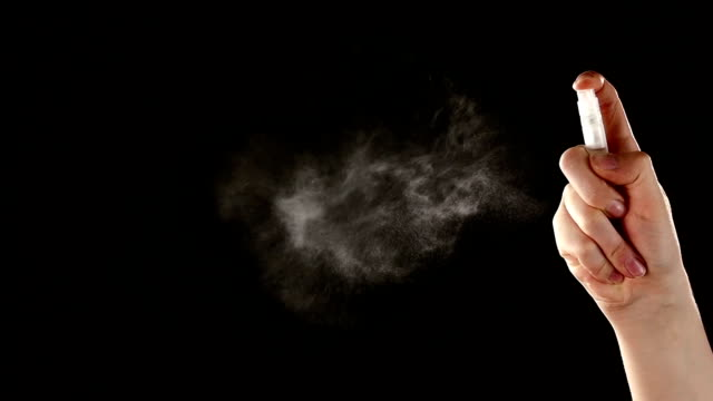 Spray bottle drops like perfume on black, slow motion video