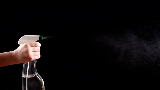 spray bottle with jet of droplets on black background, slow moti - lysol stock videos & royalty-free footage