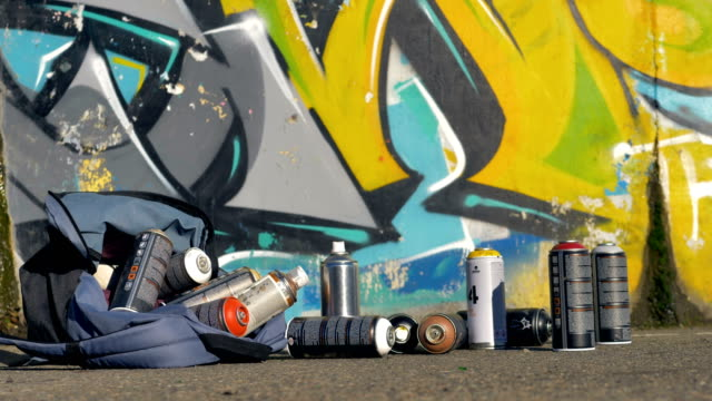 Spray paint cans fallen from a backpack on a pavement. video