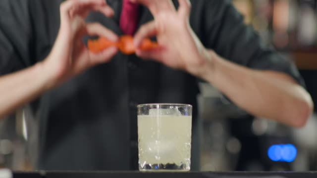 Spraying cocktail glass with twisted orange peel
