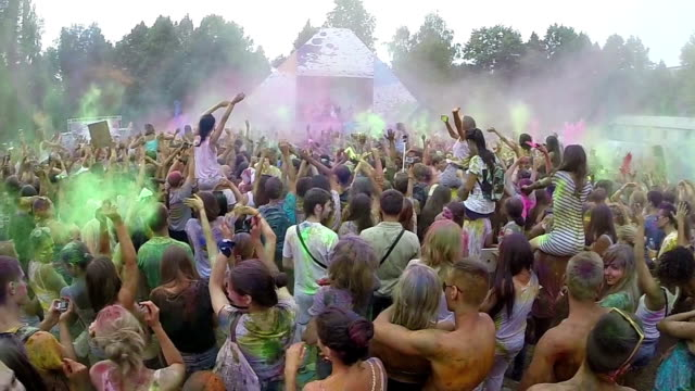 Spraying colored powder paint among crowd, festival slow motion video