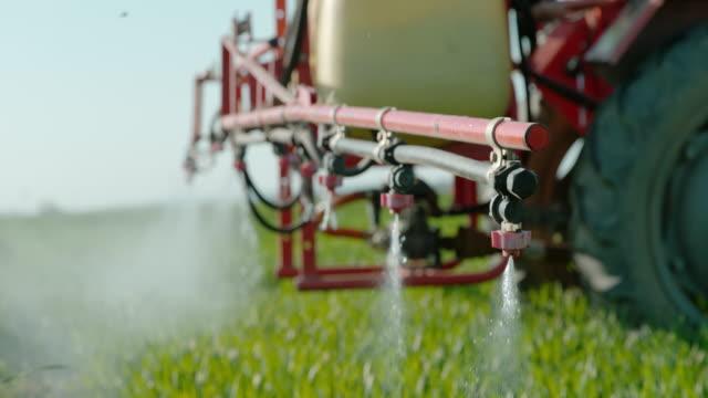 slo mo spraying pesticides on a field - insetticida video stock e b–roll