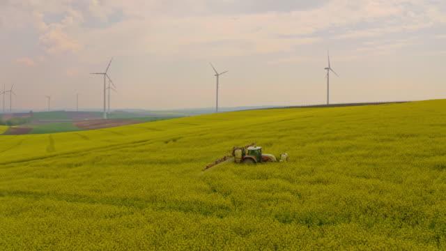 vídeos y material grabado en eventos de stock de aerial pulverización de pesticidas sobre el campo de la canola rodeado de turbinas eólicas - drone footage