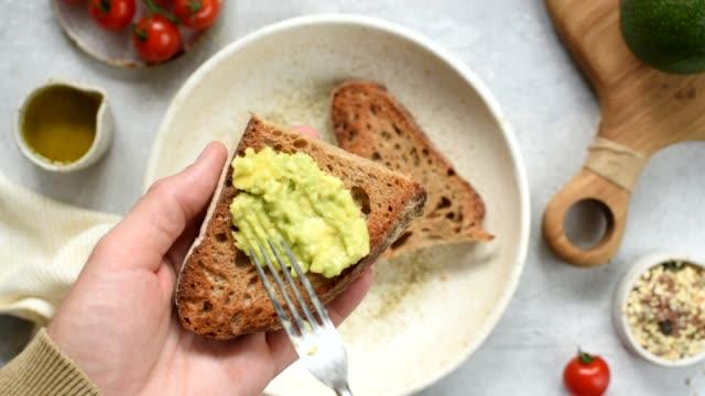 stockvideo's en b-roll-footage met verdeel avocado over geroosterd brood - geroosterd brood