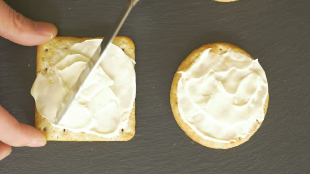 spread soft cheese on biscuit crackers