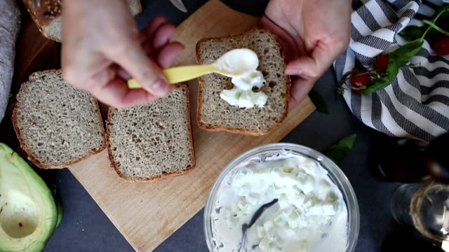 vídeos de stock, filmes e b-roll de espalhar o molho de abacate e creme azedo no pão - sem glúten