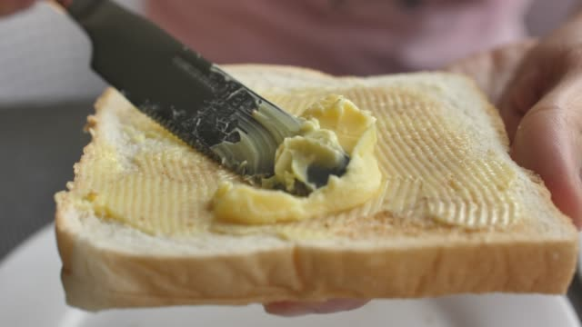 Spreading butter on a slice of bread