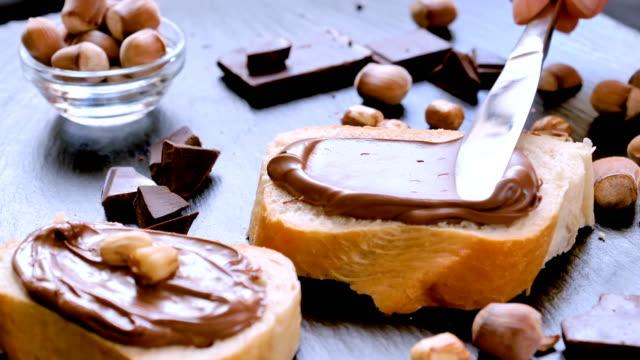 sprida hasselnöt choklad grädde på bröd närbild - brödlimpa bildbanksvideor och videomaterial från bakom kulisserna