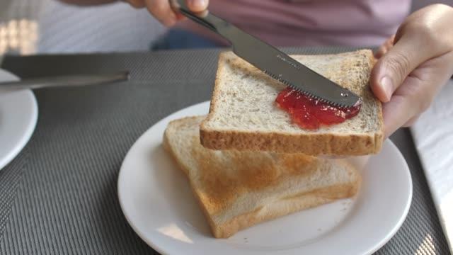 stockvideo's en b-roll-footage met spreiding van de jam op een sneetje brood - geroosterd brood