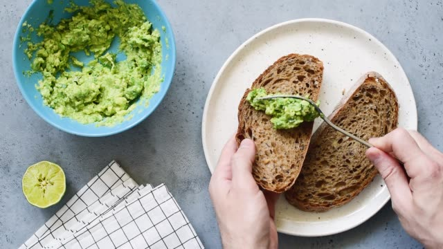 stockvideo's en b-roll-footage met het uitspreiden van gestampte avocado op geheel korrel brood - geroosterd brood