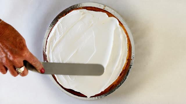 schlagsahne auf frischen käsekuchen verteilen - zuckerguss stock-videos und b-roll-filmmaterial