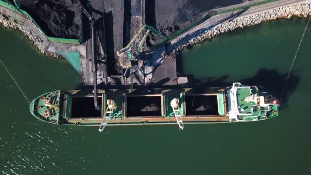 vídeos de stock, filmes e b-roll de primavera, 2019 - nakhodka, território primorsky. porto de carvão. sobrevoando um porto de carvão na pequena cidade de nakhodka. carregamento de carvão em um navio de carga no porto de carvão do mar. - vinho do porto