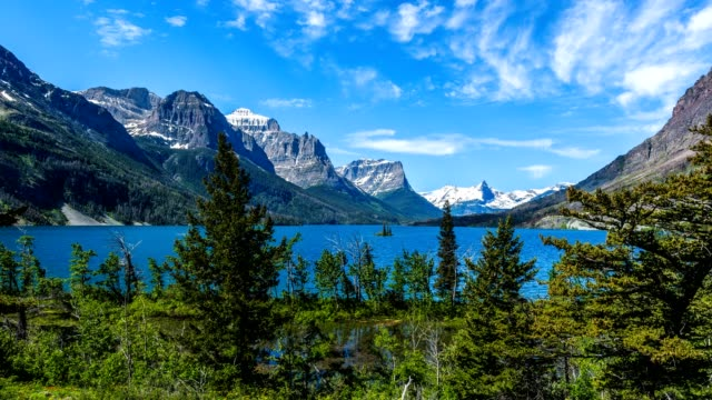 Spring at Saint Mary Lake - Time-lapse video of a panoramic view of high clouds passing over blue Saint Mary Lake and its surrounding steep mountains in Glacier National Park, Montana, USA. video