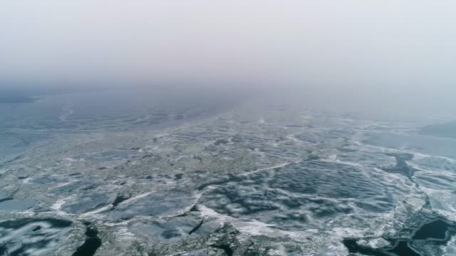 spring ice drift on the river on a cloudy day - drone collection - ghiaccio galleggiante video stock e b–roll