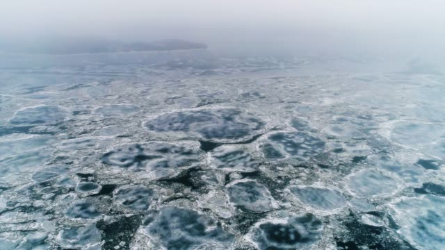 drift di ghiaccio primaverile sul fiume in una giornata nuvolosa - collezione di droni - ghiaccio galleggiante video stock e b–roll