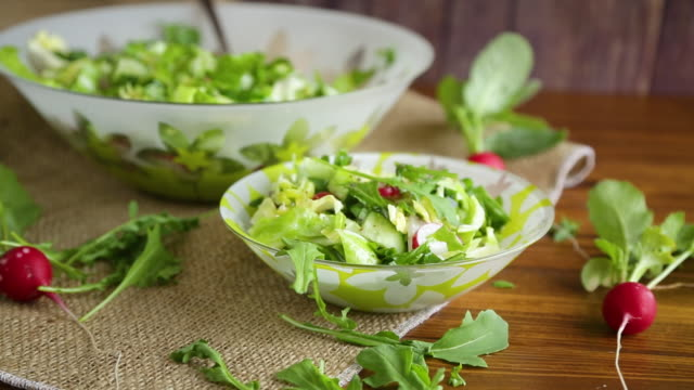 Spring salad from early vegetables, lettuce leaves, radishes and herbs in a plate on the table video