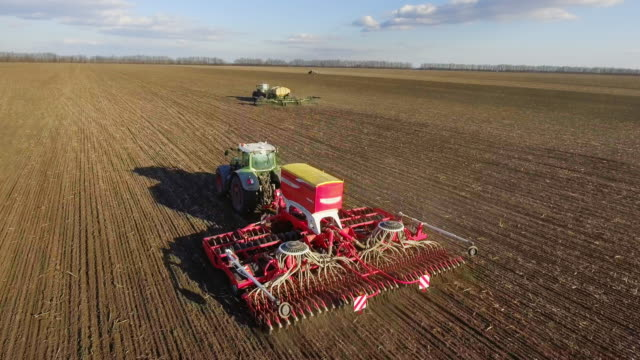 Spring sowing campaign - two tractors pull seeders, a rural landscape Spring sowing campaign - two tractors pull seeders, a rural landscape. 4K aerial video plowing stock videos & royalty-free footage