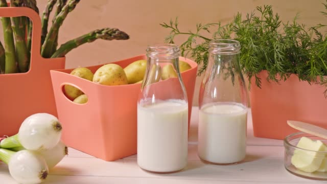 spring young vegetables in coral containers and bottles with milk on table - молодой картофель стоковые видео и кадры b-roll