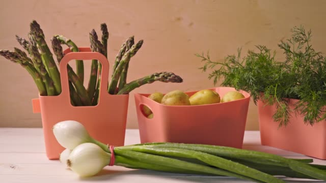spring young vegetables in coral containers on wooden table - молодой картофель стоковые видео и кадры b-roll