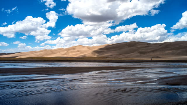 Springtime at Great Sand Dunes - White spring clouds, on blue sky, passing over rolling sand dunes and gently flowing Medano Creek. Great Sand Dunes National Park & Preserve, Colorado, USA.