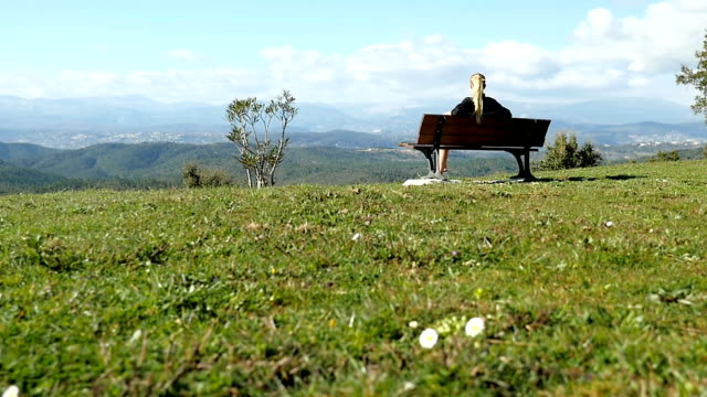 Springtime contemplation Hd slow motion over shoulder view of panoramic mountains. Rear view of young sport woman sitting and contemplating on bench in nature. Blond athlete girl resting after relaxation exercise and getting away from all of it. park bench stock videos & royalty-free footage
