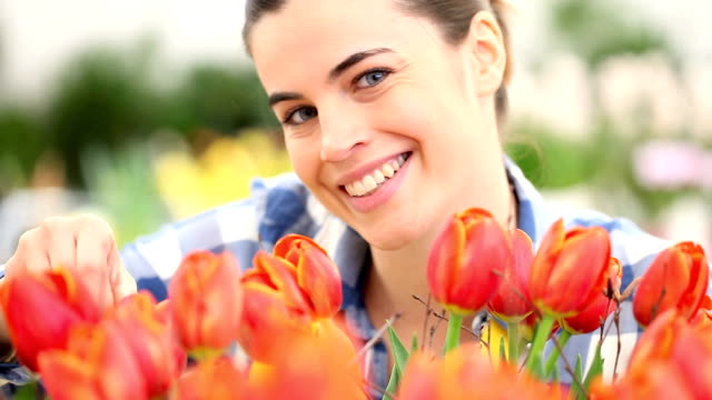 springtime, smiling woman in garden with tulips video