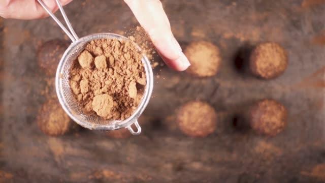 vídeos de stock e filmes b-roll de sprinkle candy cocoa powder from a small spoon-sieve - cacau em pó