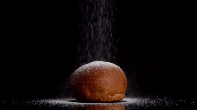 Sprinkle powder sugar on sweet bun, super slow motion on dark background. Copyspace at the top. video
