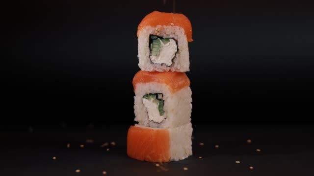 Sprinkle sesame seeds on a salmon sushi, macro video video