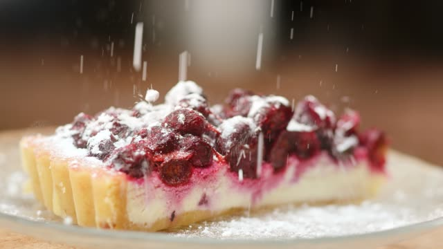 sprinkle sugar powder on rotating cheesecake slow motion. close up shot on 4k red camera - nadziewany placek filmów i materiałów b-roll