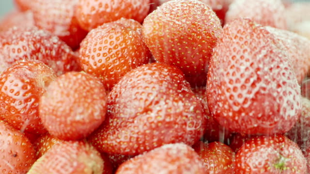 Sprinkle the red juicy strawberries with sugar. Sugar grains fall on strawberry berries, slow motion video video