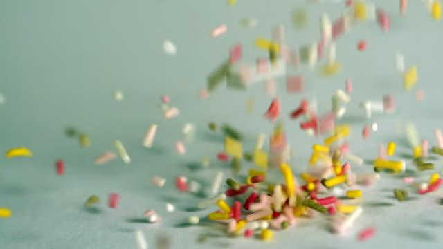 sprinkles pouring onto blue surface - confetti bildbanksvideor och videomaterial från bakom kulisserna