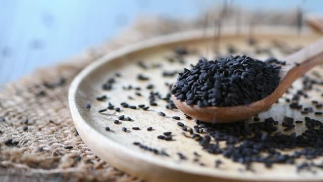 vídeos de stock, filmes e b-roll de polvilhando sementes de gergelim preto em uma colher de madeira. - formato bruto