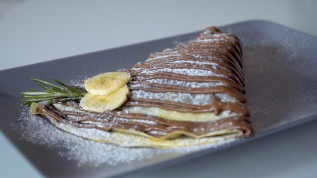 strö choklad banan pannkaka med strösocker i slowmotion - crepes bildbanksvideor och videomaterial från bakom kulisserna