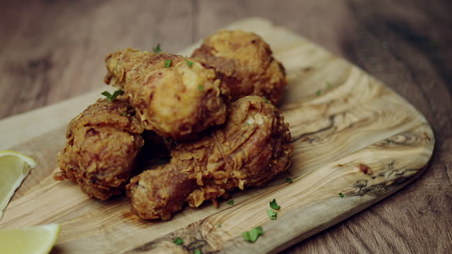 Sprinkling fresh green coriander in top of a pile of Fried Chicken/meat. Concept of serving freshly made meal.