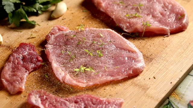 Sprinkling green thyme over raw pork meat slices video