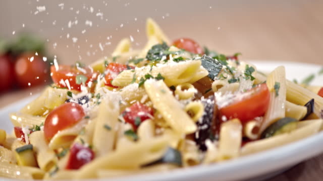 SLO MO Sprinkling parmesan over pasta with fresh vegetables Slow motion close up shot of sprinkling parmesan cheese over a delicious pasta made with fresh vegetables. cheese stock videos & royalty-free footage