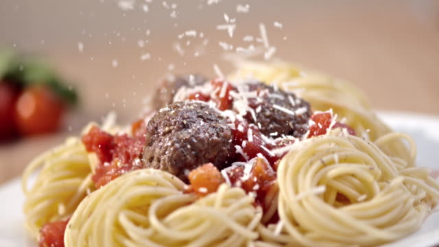 SLO MO Sprinkling parmesan over spaghetti and meatballs Slow motion close up shot of adding parmesan cheese to a spaghetti and meatballs dish nicely served on a plate. spaghetti stock videos & royalty-free footage