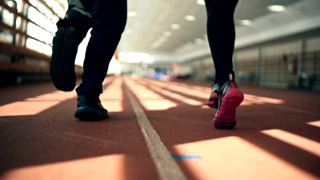Sprint Training Rear view of male and female feet in athletic shoes running in stadium tramway videos stock videos & royalty-free footage