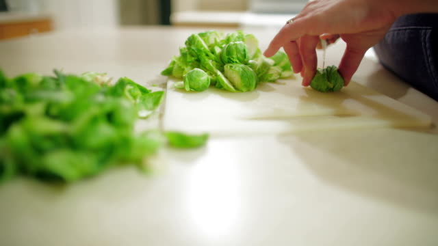 stockvideo's en b-roll-footage met sprout greens and slicing sprouts - spruitjes